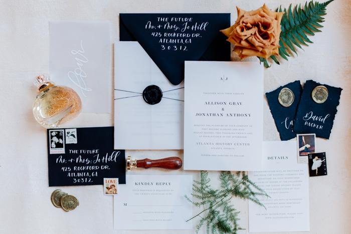 imagen plana de suite de invitación de boda de playa de arena negra