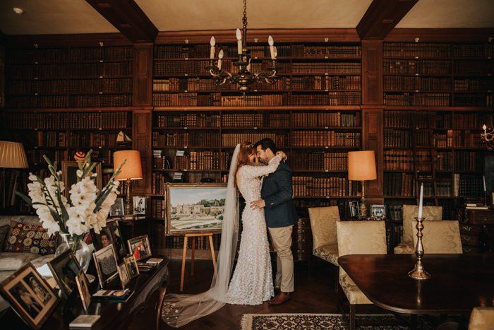 Pareja de novios de Tissington Hall besándose en la biblioteca