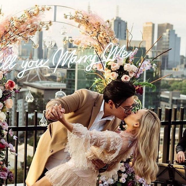 pareja besándose delante del cartel de la propuesta